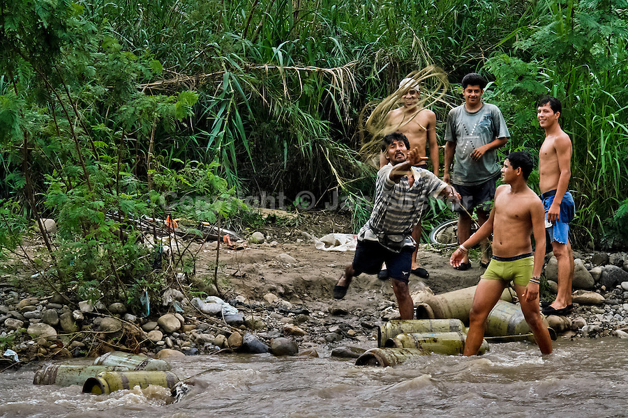 A contraband smuggler throws a rope to his workmate on the shore of the river Tachira on the Colombia-Venezuela border, 3 May 2006. Venezuelan gasoline, being 20 times cheaper than in Colombia, is the most wanted smuggling item, followed by food and car parts, while reputable Colombian clothing flow to Venezuela. There are about 25,000 barrels of gasoline crossing illegally the Venezuelan border every day. The risky contraband smuggling, especially during the rainy season when the river rises, makes a living to hundreds of poor families in communities on both sides of the frontier.
