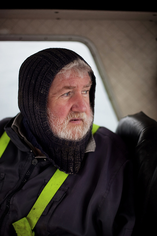 A Faroese fisherman looks out at the sea from inside of his fishing boat in the Faroe Islands.