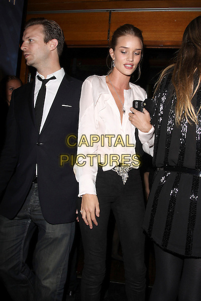 GUEST & ROSIE HUNTINGTON WHITELEY.Leaving the launch of the OMEGA Constellation 2009 collection, Berkely Street, London, England..October 15th, 2009.half 3/4 length whitley black jeans denim skinny white blouse top plunging neckline clutch bag suit jacket .CAP/AH.©Adam Houghton/Capital Pictures.