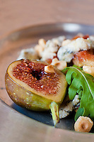 Close up of a halved fig served with a salad of blue cheese, hazelnuts and rocket