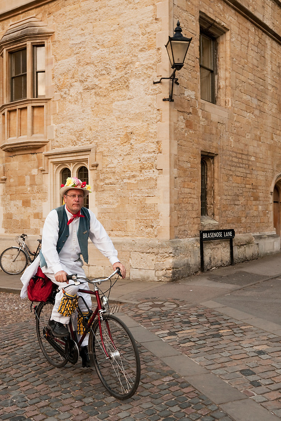 A Morris dancer navigates Oxford's Brasenose Lane by bicycle on May Morning.