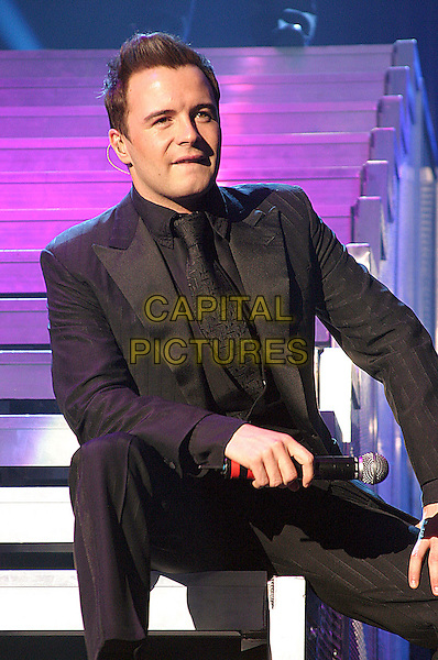 WESTLIFE.SHANE FILAN.Live in concert, Nottingham Arena, 22nd March 2005..half length sitting on steps on stage music gig .Ref: JEZ.www.capitalpictures.com.sales@capitalpictures.com.©Jez Self/Capital Pictures