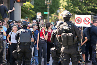 PORTLAND, OR - AUGUST 04: Hundreds from alt-left groups are kept back by police as they watch a rally by far-rights groups on August 4, 2018 in Portland, Oregon. (Photo by Karen Ducey/Getty Images)
