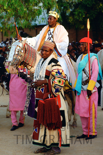 A n honoured chief riding a decorated horse with his attendants at a Durbar in Maidugari, Nigeria