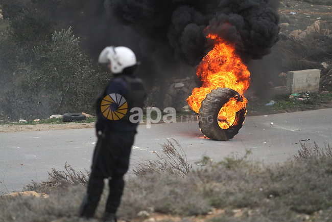 A Palestinian police officer takes position during clashes with youth from the Palestinian refugee camp of al-Jalazoun as they block the main road leading to the West Bank city of Ramallah January 12, 2014. At least 50 people were hurt on Sunday in a clash between Palestinian police and residents of the refugee camp protesting against a strike in a U.N. aid agency that has paralysed services, police and an ambulance service said. The demonstration was the most violent in a series of protests stemming from a strike for higher pay by local employees of the United Nations Relief and Works Agency (UNRWA). Photo by Issam Rimawi