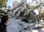 Donna Plen of Manchester, looks at the large limb that came down on the den of her Stephen Street home in Manchester, after the the record breaking snow storm brought down trees and utility wires leaving more than 700, 000 CL+P customers in the dark, Sunday, October 30, 2011. (Jim Michaud/Journal Inquirer).