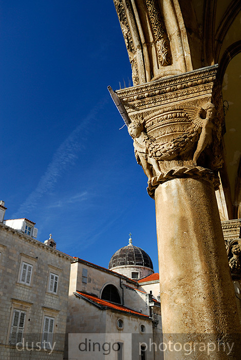 Detail of column carvings, Knezev Dvor (Rector's Palace), with dome of church of Saint Blaise (Sveti Vlaha), Dubrovnik old town, Croatia