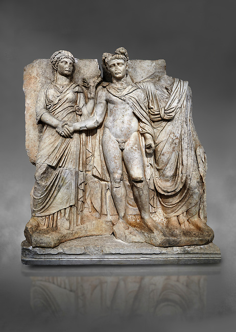 """Roman Sebasteion releif sculpture of emperor Claudius and Agrippina, Aphrodisias Museum, Aphrodisias, Turkey.  Against a grey background.<br /> <br /> Claudius in heroic nudity and military cloak shakes hands with his wife Agrippina and is crowned by the Roman people or the Senate wearing a toga. The subject is imperial concord with the traditional Roman state. Agrippina holds ears of wheat: like Demeter goddess of fertility. The emperor is crowned with an oak wreath, the Corona civica or """"citizen crow"""", awarded to Roman leaders for saving citizens lives: the emperor id therefore represented as saviour of the people."""