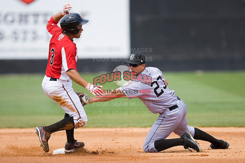Jake Kahaulelio #3 of the Carolina Mudcats beats the tag from Tim Torres #23 of the Jacksonville Suns as he slides into second base with a double at Five County Stadium May 16, 2010, in Zebulon, North Carolina.  Photo by Brian Westerholt /  Seam Images