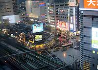 JR Yamanote line runs above Yasukuni dori avenue.  Buses and taxis on treet in shinjuku.