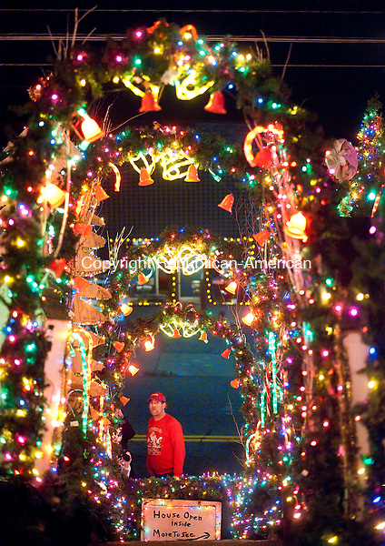 TORRINGTON, CT--- -112715JS08--Ron Merriman, owner of the Merriman Christmas House on Main Street in Torrington, talks mans the gate in front of his house during Light Up Main events in downtown Torrington on Friday. Many of the events were hosted by Torrington Parks and Recreation Department.  <br />  Jim Shannon Republican-American