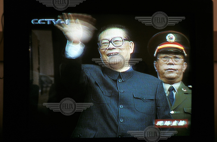 China..Propaganda - all TV channels showing single event live -50th anniversary of PRC celebrations. President Jiang Zemin waving fromTiananmen Gate with senior PLA officer behind. Jiang switching frm usual suit to Mao clothing for his attempt to step into shoes of  Mao..Mark Henley