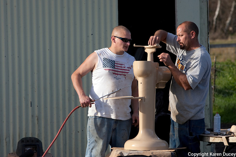 "Anthony Estrella, right, gets help from Mark Outland while restoring a cream separator at Tthe Estrella Family Creamery in Montesano,Wash.  on November 4, 2010.  ""We're just trying to live the dream"" says Anthony. ""You can see we're not exactly getting filthy rich off this.""  The Food and Drug Administration ordered the Estrella Family Creamery in Montesano,Wash.  to stop processing cheeses after it found listeria bacteria on some of the cheeses this year.  The family says they have made many renovations on the farm and the bacteria is only found on the soft cheese, not everything.  They believe they should be allowed to resume making cheese and sell the hard cheeses they have already made at the facility.  The creamery is one of Washington's most famous artisan cheesemakers.  (photo credit Karen Ducey). ."