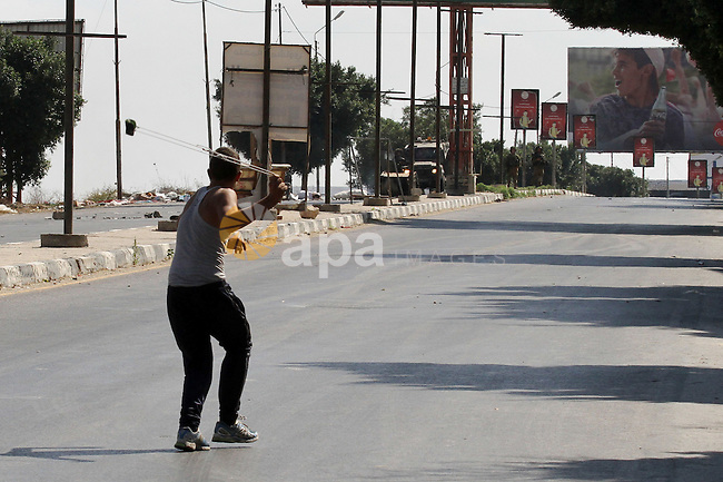 A Palestinian protester hurls stones towards Israeli troops during clashes following a protest in solidarity with Palestinian prisoners held in Israeli jails, at the Hawara checkpoint near the West Bank city of Nablus on Aug. 18, 2016. Photo by Nedal Eshtayah