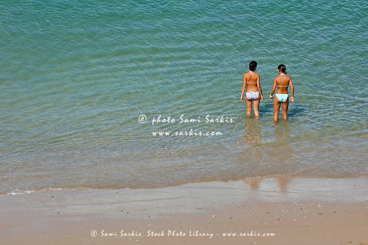 Two teenage girls bathing at the beach.