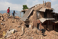 Children play while a man searchs his belongings in the rubble at Changu village,  Bhaktapur, outside of Kathmandu, Nepal. May 05, 2015