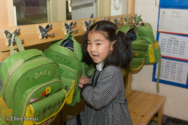 Beijing, China. The Little Oak Children's House. Private daycare and Montessori-guided early childhood education programs. Kindergarten classroom. Student (girl, age 5) hanging up her backpack in classroom. ID: AF-LOS. ©Ellen B. Senisi.