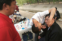 A charlatan dentist fixes a man's teeth in an open market in Beijing, China..02 May 2007