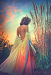 Blonde woman walking away in a backless rainbow dress into the colorful sunset.