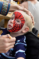 A boy having his face painted.