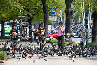 Women sell bags of bird seed to tourists on the streets of Bangkok, Thailand