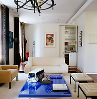 This elegant living room is furnished with designer pieces and a space saving cupboard with a sliding door