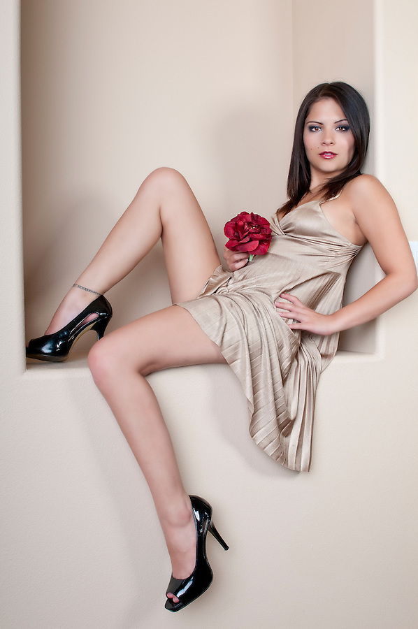 Young woman seated and relaxing with a rose in hands and sensual dress.