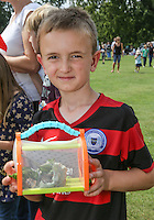 2014 World Championship Snail Racing in Congham (Norfolk)<br /> Picture description:<br /> Owners of snail and trainer love to accessorise for the event aND some carry their snail in fancy carriers<br /> General infos:For more than 25 years the World Snail Racing Championships have been held at Congham, near King's Lynn, in Norfolk.Before snails can enter a race a sticker with a number must be put on so they can be identified. The snails race from the centre of a circle to the outside. The circle has a radius of 13 inches. The snails are put in the middle and pointed in the right direction.The  Snail Master Neil starts the races. He shouts: &quot;Ready, steady, SLOW!&quot; And off dash the snails! The Snail Master keeps the course well-watered as snails like damp conditions.Races are held on a table covered with a white cloth. Machine a circle, with braid in the middle, and then machine a similar circle 13 inches away.Owners do dress up. The World record stands at 2 minutes over the 13 inches. It was set up in 1995 by a snail called Archie. The record can only be challenged at the World Championships at Congham.Giant foreign snails are not allowedOften owners like to give their snails names like Speedy or Schumacher!<br /> Picture by Marcello Pozzetti &copy; IPS PHOTO AGENCY<br /> Cavell Barn<br /> The Common<br /> Swardeston<br /> Norwich<br /> Norfolk<br /> NR14 8DZ<br /> T 01508 571 480<br /> M 07973308835