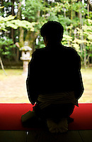 A Japanese man in a black kimono sits in the formal kneeling position to drink tea at Koto-in Temple, Daitokuji, Kyoto.