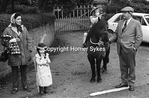Hatherleigh Fire Festival. Hatherleigh, Devon England 1973. Childrens parade in afternoon. November. Playing Cowboys and Indians.   My ref 5/640/1973