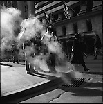 People paused on the corner of Wall Street opposite the New York Stock Exchange as steam from a street drain was illuminated by the lunchtime sunshine. New York City, New York, November 12, 2008