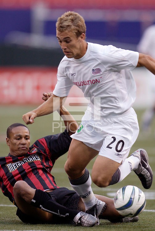 the Revolution's Taylor Twellman gets past the tackle of the MetroStars' Ricardo Clark. The New England Revolution were defeated by the MetroStars 3 to 2 on Saturday September 11, 2004 at Giant's Stadium, East Rutherford, NJ..