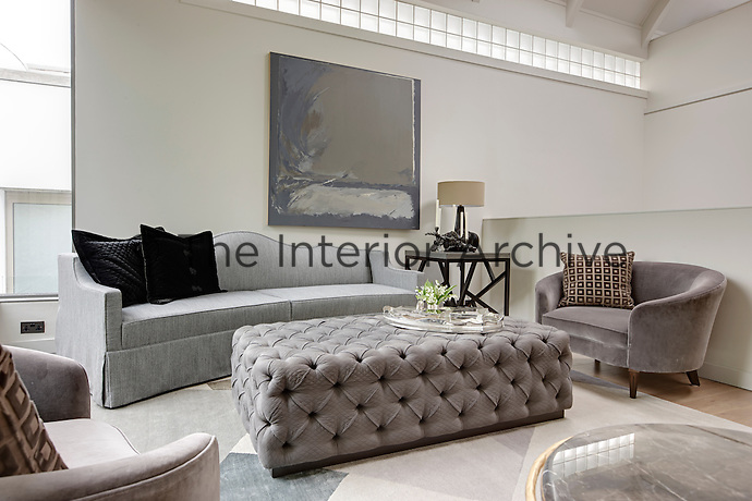 A sitting room with a grey sofa and two tub armchairs are arranged around an upholstered ottoman used as a coffee table.  A lamp and a candelabra stand on a side table.