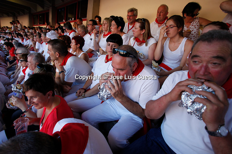 People eating during one of the San Fermin bullfight, in Pamplona, northern of Spain.  San Fermin festival is worldwide known because the daily running bulls.