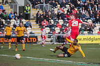 Billy Kee of Accrington Stanley shoots under pressure from Janoi Donacien of Newport County during the Sky Bet League 2 match between Newport County and Accrington Stanley at Rodney Parade, Newport, Wales on 28 March 2016. Photo by Mark  Hawkins.