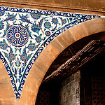 Iznik 17 - Triangular Iznik tile infill panel between arches, featuring stylized flower, leaf and animal motifs. Rustem Pasa Mosque, Eminonu, Istanbul, Turkey