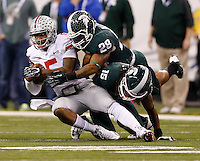 Michigan State Spartans linebacker Denicos Allen (28) and cornerback Trae Waynes (15) tackle Ohio State Buckeyes quarterback Braxton Miller (5) but not after he made a first down during the second quarter of the Big Ten championship football game at Lucas Oil Stadium in Indianapolis on Dec. 7, 2013. (Adam Cairns / The Columbus Dispatch)
