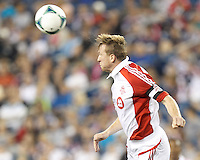 Toronto FC defender Steven Caldwell (13) heads the ball.  In a Major League Soccer (MLS) match, Toronto FC (white/red) defeated the New England Revolution (blue), 1-0, at Gillette Stadium on August 4, 2013.