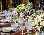 Details of a table setting in the Dining Room at Blickling Hall. Soup plates await soup and glasses some wine and a bowl of fruit and bowls of lilies adorn the centre of the table.