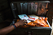 Maina Devi shows the securely kept trunk of documents in her hut in Bhelaiya village in Raxaul, Bihar, India.
