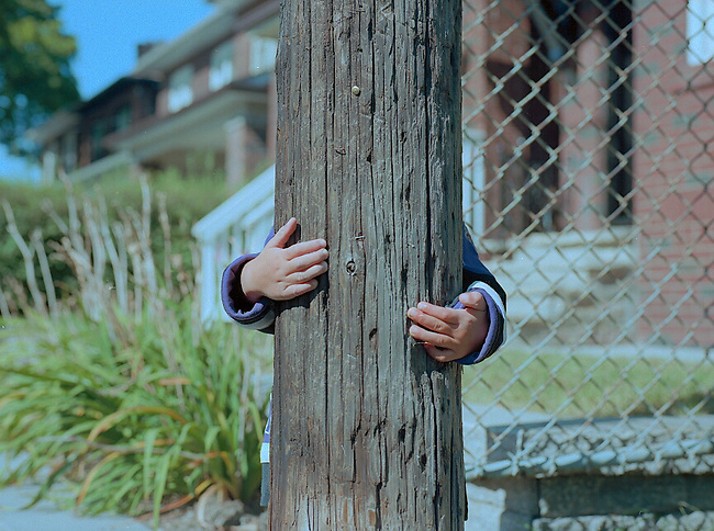 A boy poses behind a wooden pole