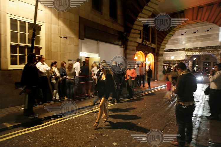 A young woman in high heels and a short skirt walks through a street past a queue of people outside a club in Piccadilly, Central London at night.