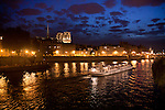 Paris at night on the Seine, with the Cathedral of Notre Dame and the Concierge Prison in the background.  A Dinner Cruise Barge is departing on the right.