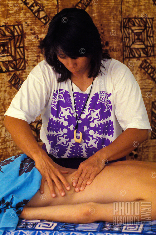 Hawaiian woman giving a lomilomi massage with kapa cloth hanging behind her