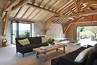 The living room is elevated above the kitchen/dining area in a space of its own, though a glass wall maintains the open-plan feel of the barn