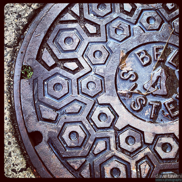 The sun peeked out of the clouds for a few minutes in the afternoon lighting up the tiny puddle in this manhole cover on Pomona Street in Germantown, January 29, 2013.