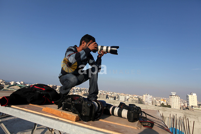 A Palestinian photographer takes pictures on a building in Gaza city, on November 20, 2012. Two Palestinian journalists were killed in an Israeli airstrike on Gaza City Tuesday evening, after media buildings were hit by Israeli warplanes two days in a row.  Photo by Majdi Fathi