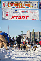 Hans Gatt and team leave the ceremonial start line at 4th Avenue and D street in downtown Anchorage during the 2014 Iditarod race.<br /> Photo by Jim R. Kohl/IditarodPhotos.com