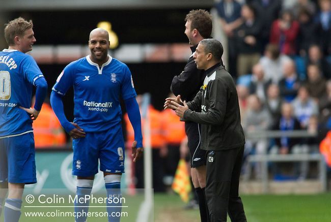 Former Coventry striker Marlon King (centre) sharing a joke with his manager Chris Hughton during the first half at the Ricoh Arena, as Coventry City hosted Birmingham City in an Npower Championship fixture. The match ended in a one-all draw, watched by a crowd of 22,240. The Championship was the division below the top level of English football.