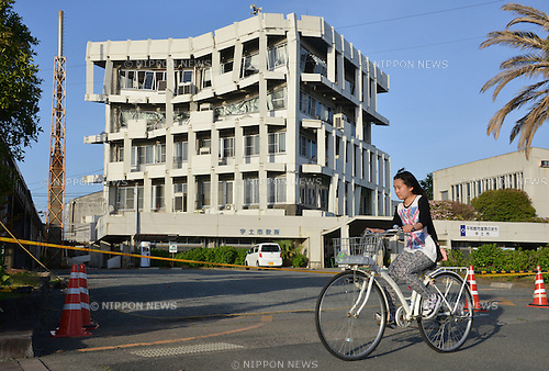 April 17, 2016, Kumamoto, Japan - A cyclist passes before a partially collapsed city hall at Uto city in Kumamoto prefecture on Sunday, April 17, 2016. More than 40 people died and some 1,000 injured as massive earthquakes attacked Japan's southern island of Kyushu. (Photo by Yoshio Tsunoda/AFLO) LWX -ytd-
